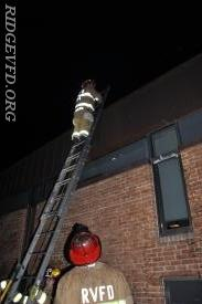 "Lt. Andrews demonstrates a proper method of setting a ladder for his ""custom"" rooftop ops."