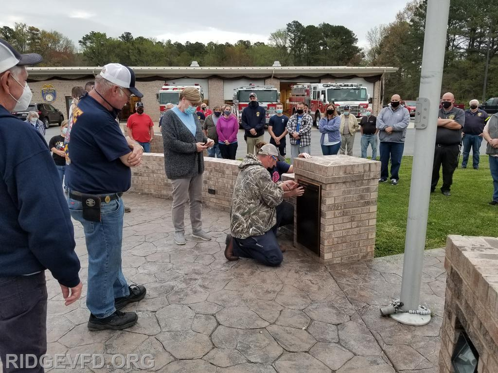 L-R: Timmy's brother (Incident Safety Officer Heavy Ridgell), wife (Associate Member Bonnie Ridgell), son (Engineer John Ridgell), and daughter (Auxiliary Member Ashleigh Andrews).  John and Ashleigh attaching nameplate to the plaque.